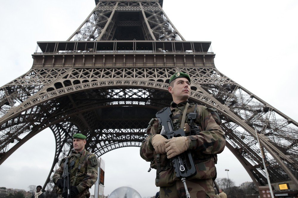 French soldiers patrol in front of the Eiffel Tower on January 7, 2015 in Paris as the capital was placed under the highest alert status after heavily armed gunmen shouting Islamist slogans stormed French satirical newspaper Charlie Hebdo and shot dead at least 12 people in the deadliest attack in France in four decades. Police launched a massive manhunt for the masked attackers who reportedly hijacked a car and sped off, running over a pedestrian and shooting at officers. AFP PHOTO / JOEL SAGET